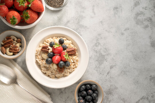 Oatmeal porridge with fresh berries blueberry and strawberries in white bowl on grey background.