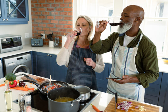 Happy senior diverse couple in kitchen wearing aprons, cooking together, drinking wine