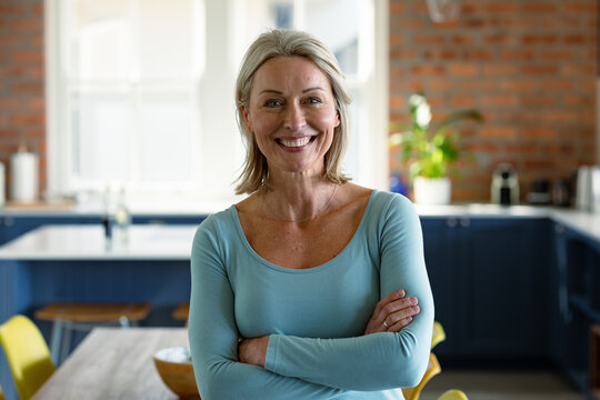 Portrait of happy senior caucasian woman in kitchen, looking at camera and smiling