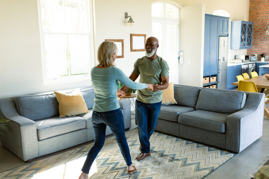 Happy senior diverse couple in living room dancing together