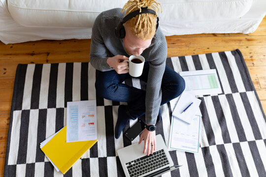 Albino african american man sitting on the floor and working from home using laptop