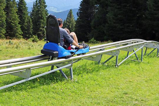 Father and son enjoying a summer fun roller alpine coaster ride