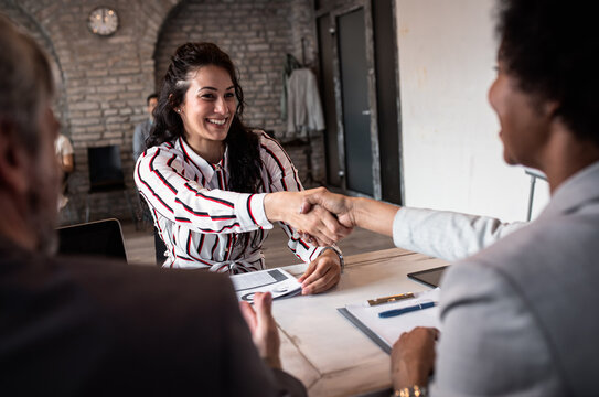Young woman shakes hands with employer at job interview.