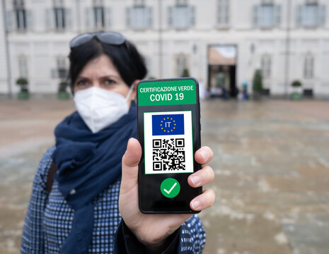 Young Italian woman holding smartphone with Green Pass QR code confirm vaccination coronavirus covid-19. Vaccine done with passport