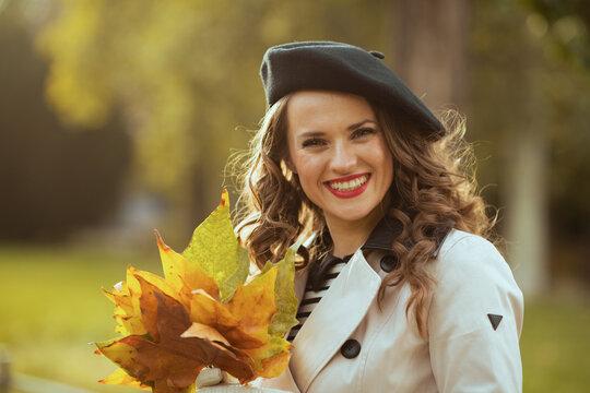 Portrait of happy trendy woman in beige trench coat