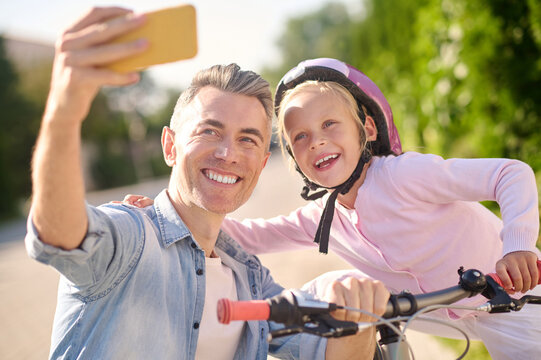 Daughter with bike and dad taking selfie on smartphone