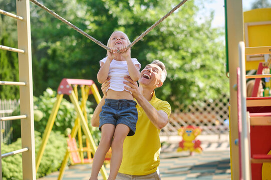 Man supporting little daughter exercising on tightrope
