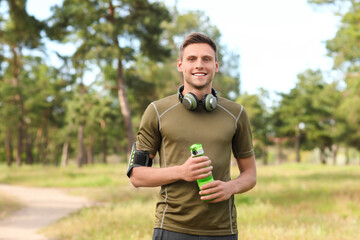 Obraz Sporty young man with bottle of water and headphones in park - fototapety do salonu