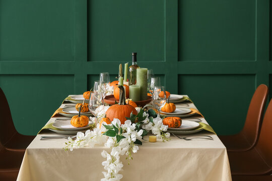 Autumn table setting with fresh pumpkins and flowers near green wall