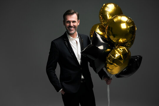 Studio shot of elegant middle aged caucasian man holding golden balloons