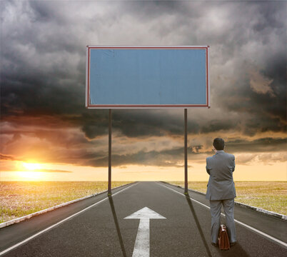 A businessman on the road next to a white arrow sign painted on the asphalt looks at a large empty billboard