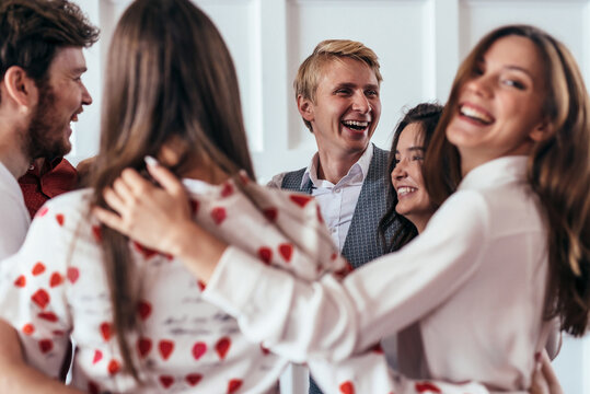 Circle of friends, funny young people hug and laugh