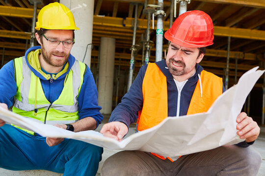 Architect and construction worker look at construction drawing