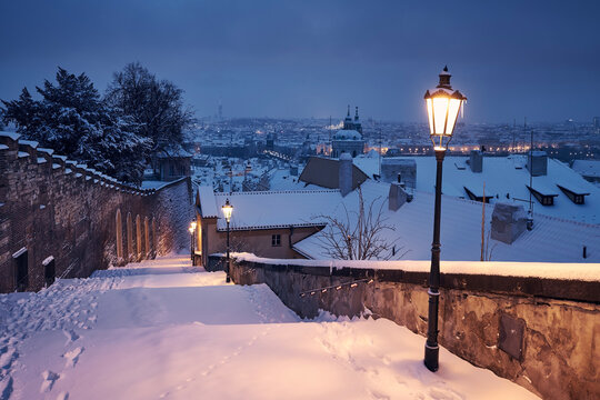 Cityscape of Prague in winter. Snow covered staircase against Lesser Town early morning.