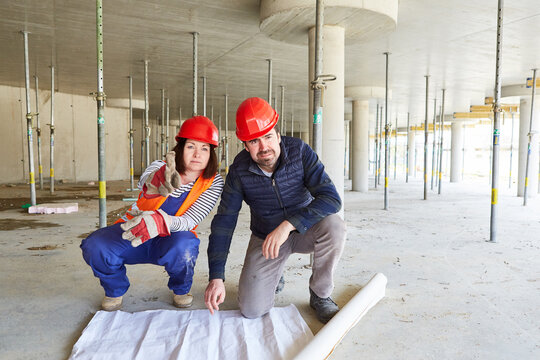 Worker and architect with floor plan on a construction site