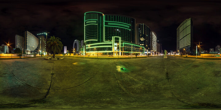 BATUMI, GEORGIA - SEPTEMBER 2021: full seamless spherical night 360 panorama on square among modern glowing skyscrapers and office buildings in equirectangular projection, for VR AR content