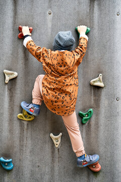 Small boy climbing a rock wall at playground