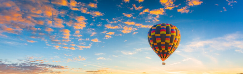 balloon and sky,Multicolored hot air balloons at sunset sky for your billboard of a travel agency or wide banner, brigth colors and soft sun light.