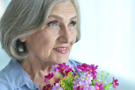 Happy senior woman at home with flowers