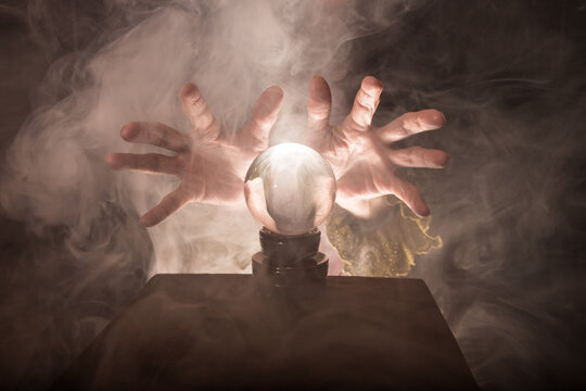 A fortune teller's hands conjure up a crystal ball. Smoke can be seen against a dark background.