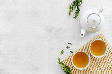 Fototapeta Asian food and drink background white teapot and black tea in two cups obraz