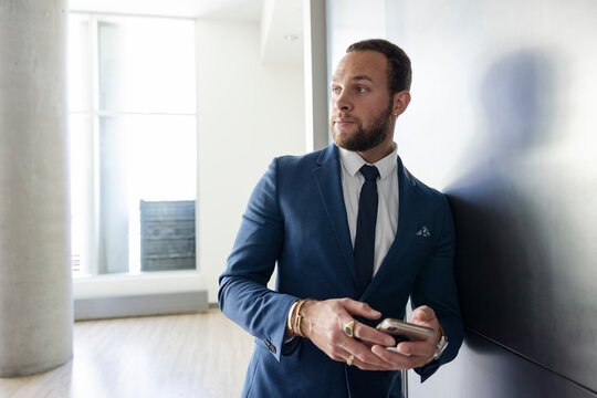 Confident businessman in suit using smart phone in office