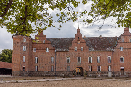 the danish Holsteinborg Castle and courtyard under green beech branches