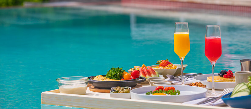 Breakfast in swimming pool, floating breakfast in luxurious tropical resort. Table relaxing on calm pool water, healthy breakfast and fruit plate by resort pool. Tropical couple beach luxury lifestyle