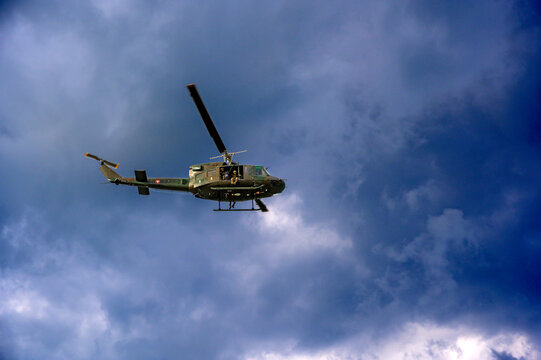 helicopter of the Austrian Armed Forces flying before a dark cloudy sky at a manoeuver, Austria