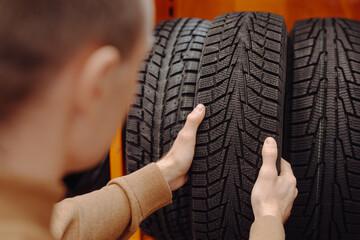Fototapeta Unrecognizable man chooses winter car tires in the auto shop obraz
