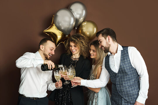 Well dressed party people celebrating  holiday or event and drinking sparkling wine