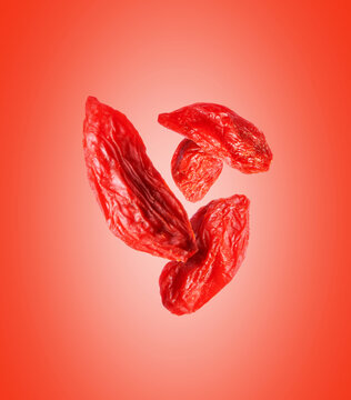 Dried goji berries close up in the air on a red background