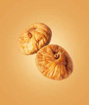 Dried figs close up in the air on a yellow background