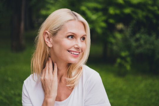 Photo of mature optimistic blond lady look wear white t-shirt in park alone