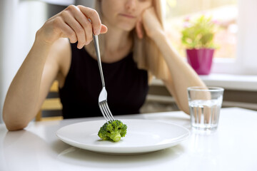 Obraz dieting problems, eating disorder - unhappy woman looking at small broccoli portion on the plate - fototapety do salonu