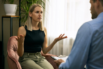 Fototapeta psychotherapy - male psychotherapist or psychiatrist conducting counselling with young woman. mental health disorder obraz