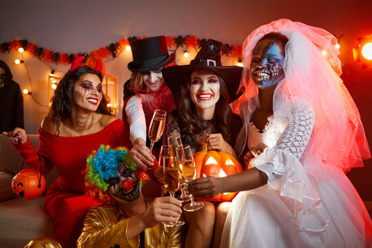 Happy young multiracial people drinking and having fun at Halloween party at home. Diverse group of smiling adult male and female friends in festive costumes sitting on sofa and clinking flute glasses