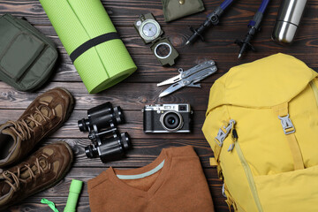 Fototapeta Flat lay composition with backpack and other camping equipment for tourism on wooden background obraz