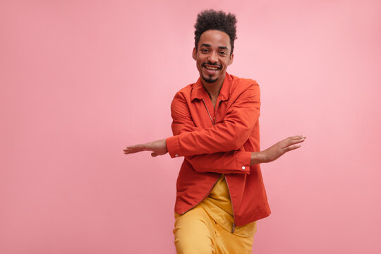 Active cute african guy with smile on his face posing on pink background. Man with amazing new Afro haircut in trendy outfit made from carrot jacket and vintage lemon jeans.