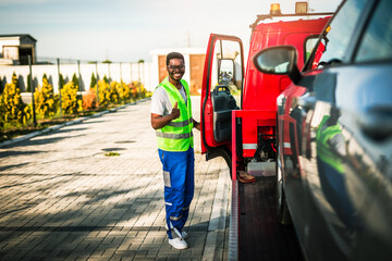 Obraz Handsome young African American man working in towing service on the road. Roadside assistance concept. - fototapety do salonu