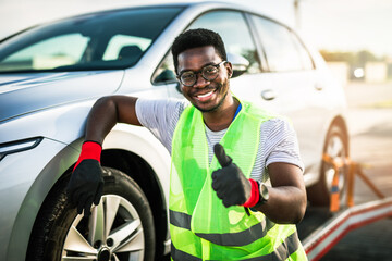 Fototapeta Handsome young African American man working in towing service on the road. Roadside assistance concept. obraz