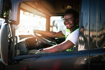Fototapeta Young handsome African American man working in towing service and driving his truck. obraz