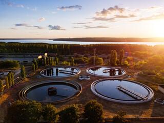 Fototapeta Modern sewage treatment plant. Round wastewater purification tanks at sunset, aerial view obraz