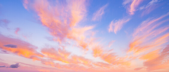 Fototapeta Stunning romantic and relaxing sunrise with some pink illuminated clouds moving across a blue sky. Long exposure, natural background. obraz