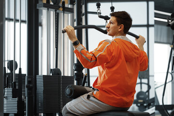 Fototapeta premium Young man working out training back muscles in the gym