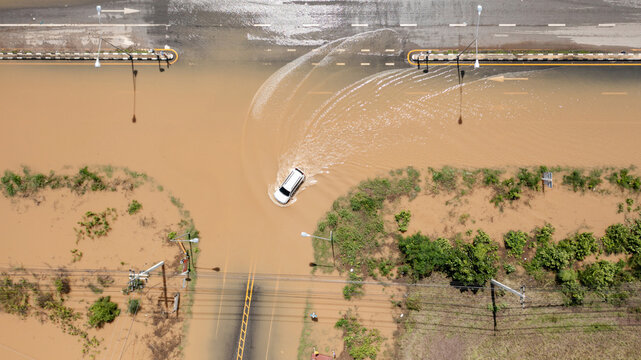 Aerial top view of Flooded the village and Country road with car, View from above shot by drone