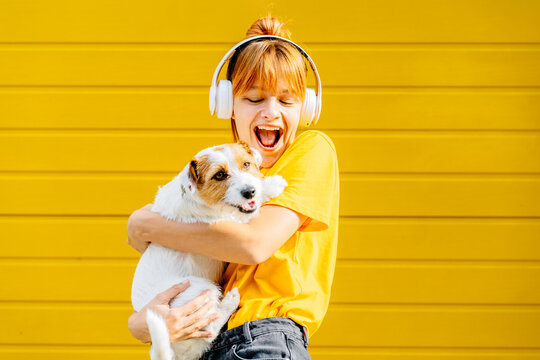 Pretty amazing she hold dog lady cool look glad mouth open laugh laughter wearing casual yellow t-shirt, listen music with headphones isolated yellow bright vibrant vivid background outdoor shot.