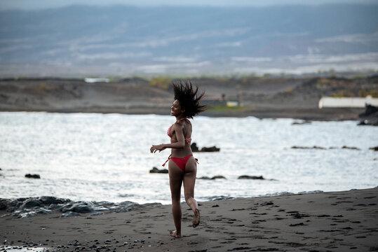 Woman in bikini in a volcanic beach