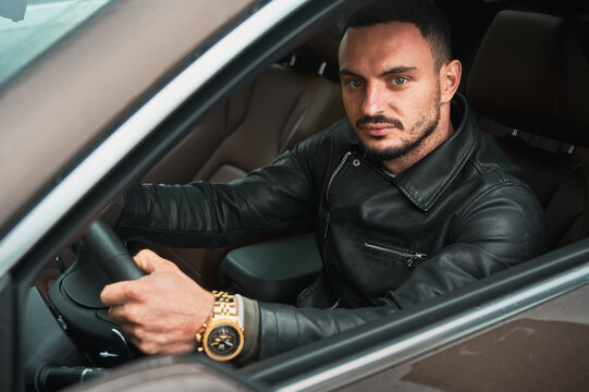 Portrait of handsome young man driving modern car. Guy driver wearing casual clothes and gold watch.