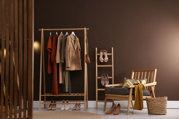 Fototapeta Modern dressing room interior with clothing rack and comfortable armchair obraz